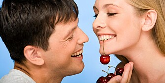 Portrait of young woman holding a cherry by teeth with man near by