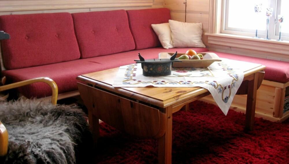 HELT PERFEKT: Sofaen er hjemmesnekret, med spesialsydde puter. Slik er den tilpasset den lille hytta slik at funksjonaliteten er optimal.