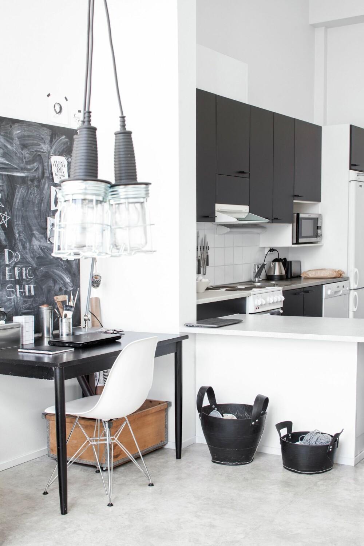 SPENNENDE MIKS: Det er åpen løsning mellom kjøkkenet og stuen. De svarte kurvene er laget av resirkulerte dekk. Her oppbevarer Netta hundeutstyret sitt. Lignende  får du blant annet hossolfang.no. I et hjørne av stuen har Netta en arbeidskrok med en stor tavle. Stolen Eames side chair bruker hun både her og ved kjøkkenbordet. Skrivebordslampen er fra Ikea. FOTO: KATJA LÖSÖNEN