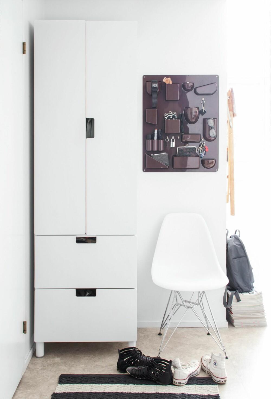 OPPBEVARING: I entreen står et enkelt hvitt Ikea-skap til ytterklær. Den vegghengte oppbevaringen Utensilo er en designklassiker fra Vitra. Til tross for at paret leier boligen har de lykkes med å sette sitt eget preg på den. FOTO: KATJA LÖSÖNEN