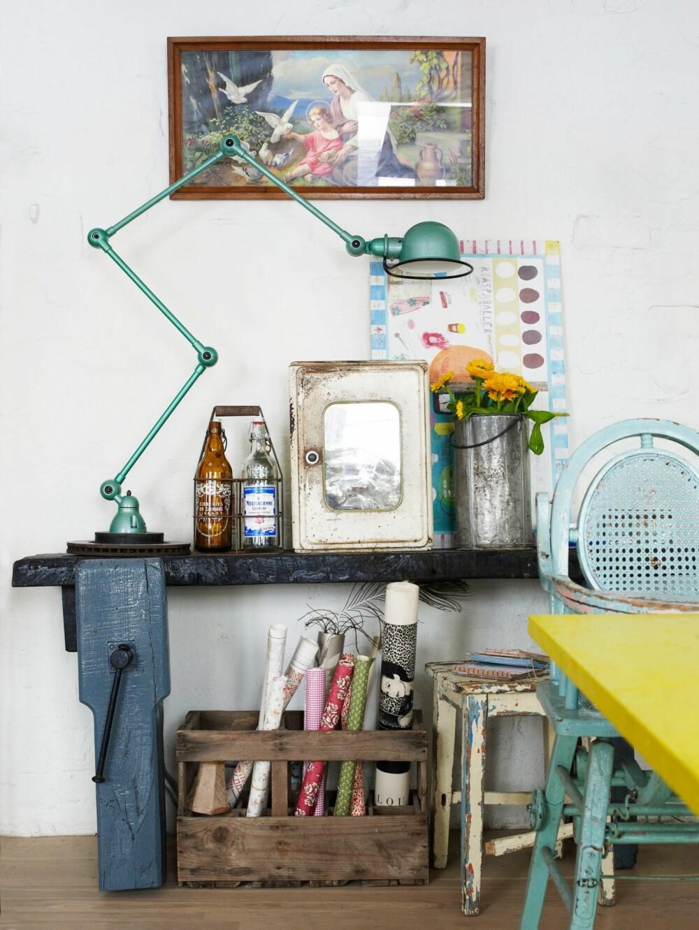 VAKKERT STILLEBEN: Det er mange stilleben i det gamle huset. Dette består av en dreiebenk, en Jielde-lampe, et medisinskap, et religiøst bilde, en blikkbøtte og limonade- og ølflasker, alt kjøpt brukt i Frankrike. Bak til høyre står Ninas eget design, barndommens oppskrifter på kleppmelk og raspeballer.