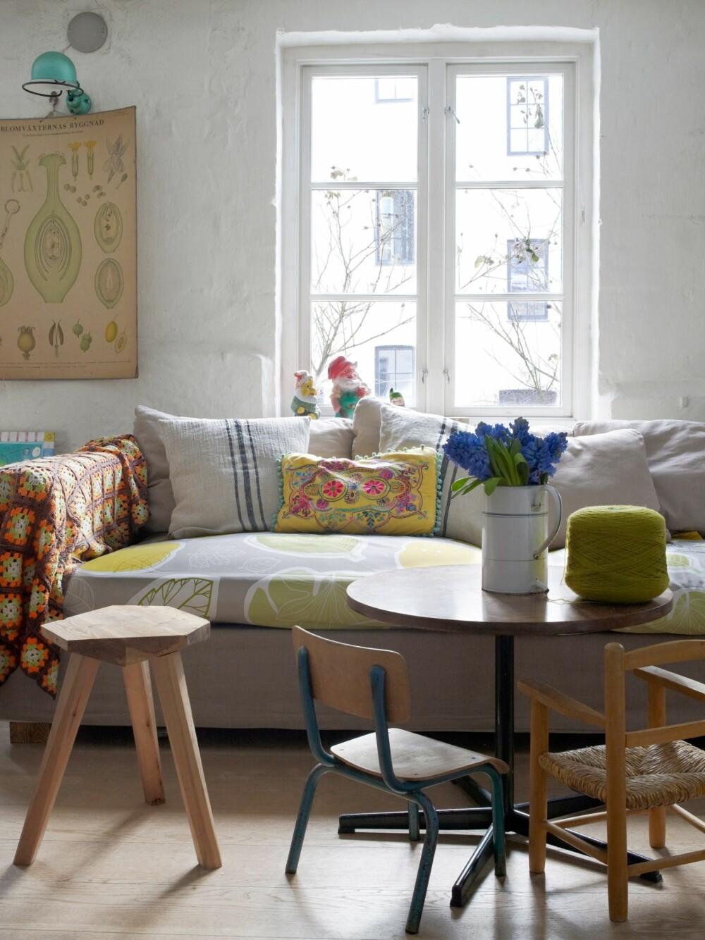 SOFAKROKEN: Sofaen fra Room er en av de få  nye tingene Nina har kjøpt, for mange år siden. Tekstilene  er fra Ikea, det heklede pleddet fra Frankrike. Den turkise  Jielde-lampen lyser opp plansjen Nina har kjøpt på Møllergata  skole, der sønnen er elev. En fransk sykehusmugge er  blitt en fin vase. Bordet er et norsk bruktfunn, de to barnestolene er kjøpt i Frankrike og krakken er laget av Ninas datter.