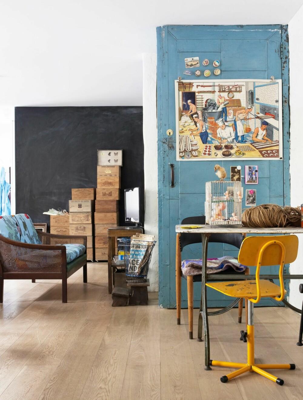 FRANSKE SKATTER: Metalldøren opp til andre etasje er et perfekt bakteppe for de franske skattene. Didier har kjøpt sofaen på Fretex, og putene er trukket med stoff fra Ikea. De gamle vinkassene selger de mye av, både til vinsamlere og til folk som vil lage bokhylle av kassene. Den gule stolen reddet Nina fra en container her hjemme, den svarte stolen fulgte med huset.