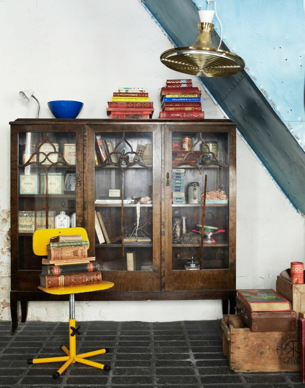 MANGE SKATTER: Det gamle familieskapet under trappen rommer franske skatter. På toppen ligger en blanding av franske bøker og norske kokebøker. 60-tallslampen i taket er kjøpt på loppemarked i Norge.