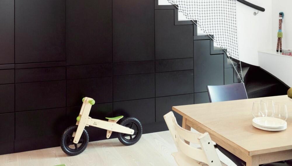 SKJULTE FUNKSJONER.Trappen er bygget av svartbeisede mdf-plater. I enden svinger den seg mot kjøkken og spisestue. Skapveggen under trappen rommer kjøkkensaker.