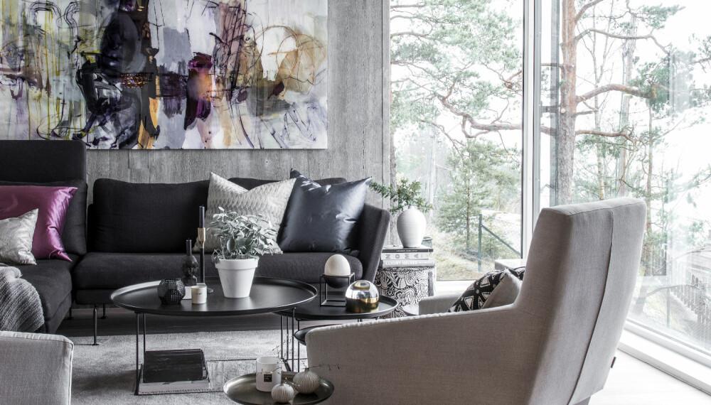 KONTRASTER: Den røffe betongveggen er laget ved hjelp av treforskaling, slik at den har fått en tøff plankeeffekt. Sofaen er designet av Antonio Citterio, sofabordet Fat Table er designet av Patricia Urquiola, gulvteppet er fra Phenomen interiørdesign/Camelia, og de beige stolene er fra spanske Sancal.