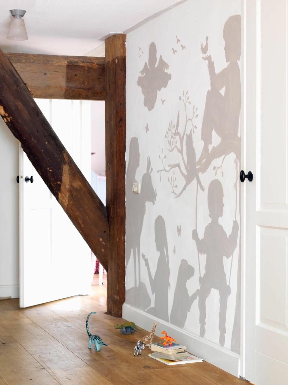 KUNST: Veggen i andre etasje er dekorert av husets kunstner. Modellene er selvsagt de fire barna. Hun fotograferte dem først, og laget deretter en collage av silhuettene.