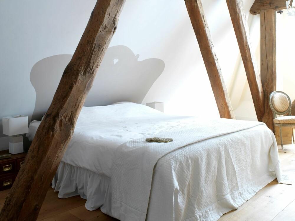 MALT SENEGJERDE: Sengen på hovedsoverommet er kilt på plass mellom to bjelker. Skråveggene gjør at det ikke er plass til sengegjerde, derfor har Ankie malt et rett på veggen.