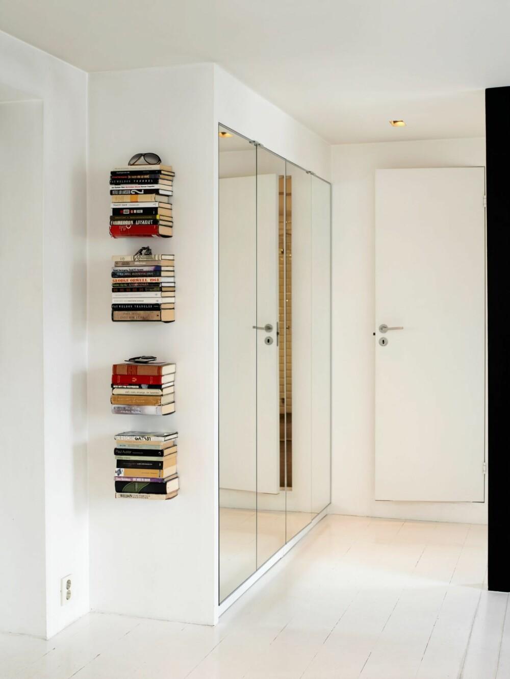 VEGGHENGTE BØKER VED INNGANGSDØREN: Bøkene i gangen tres rett på de tynne bokhylleplatene. Slik synes bøkene å henge rett på veggen. Oppbevaringsbehovet man har i enhver entré finner sin løsning i speilgarderoben.