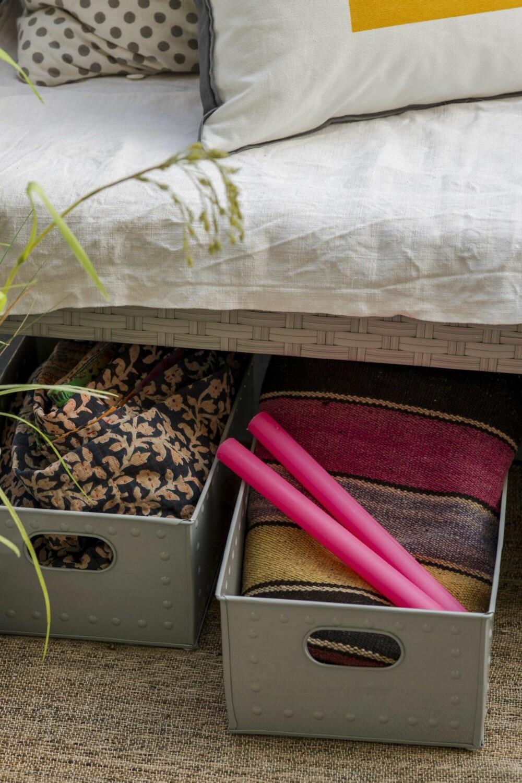 SNIK INN LITT OPPBEVARING: Praktiske metallkasser under sofaen, kr 229 pr. stk., Kremmerhuset. I kassen til venstre ligger et indisk vintage pledd, kr 1350, Bon Dep. I kassen til høyre et vintage kelimteppe, kr 2499, og neonlys, kr 25 pr. stk., alt fra Bolina.