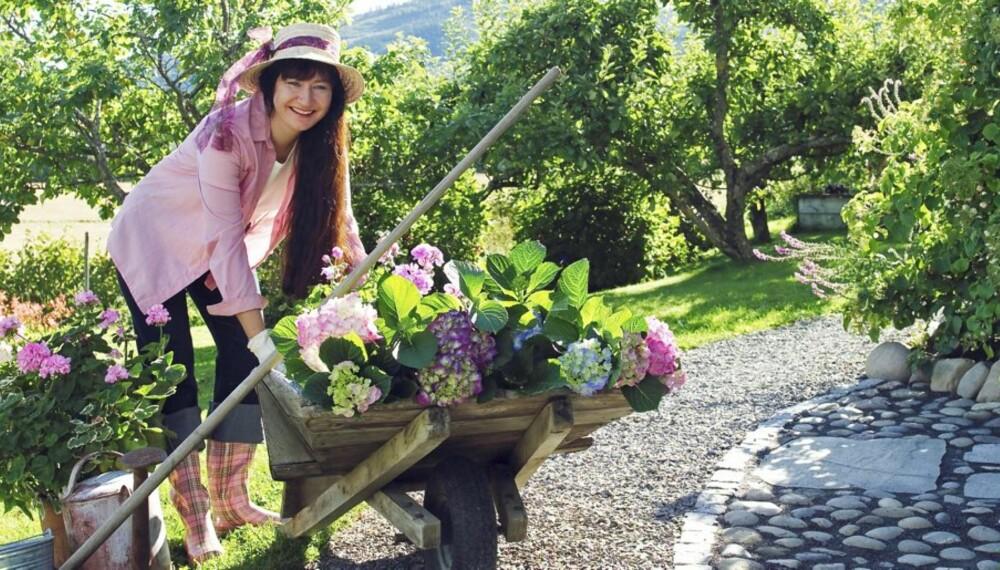 FORNØYD MED HAGEN: Klar for å plante i hage med grus og steinheller.