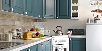 BONDEBLÅTT: Den friske blåfargen og det gråbeige gulvet gir en harmonisk og rustikk følelse. Hytteeierne fikk ideen til den skråstilte komfyren fra et kjøkken i Hytteliv. Med den får de utnyttet benkeplassen maksimalt.
