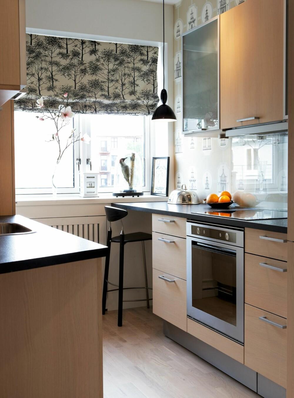 FIFFIG. Liftgardinene og tapetet har mønster i diskret fargenyanser som fungerer sammen. Sprutpanel i glass over kjøkkenbenken. I hjørnet ble det plass til et arbeidsbord. Kjøkkeninnredning og barkrakk fra HTH.