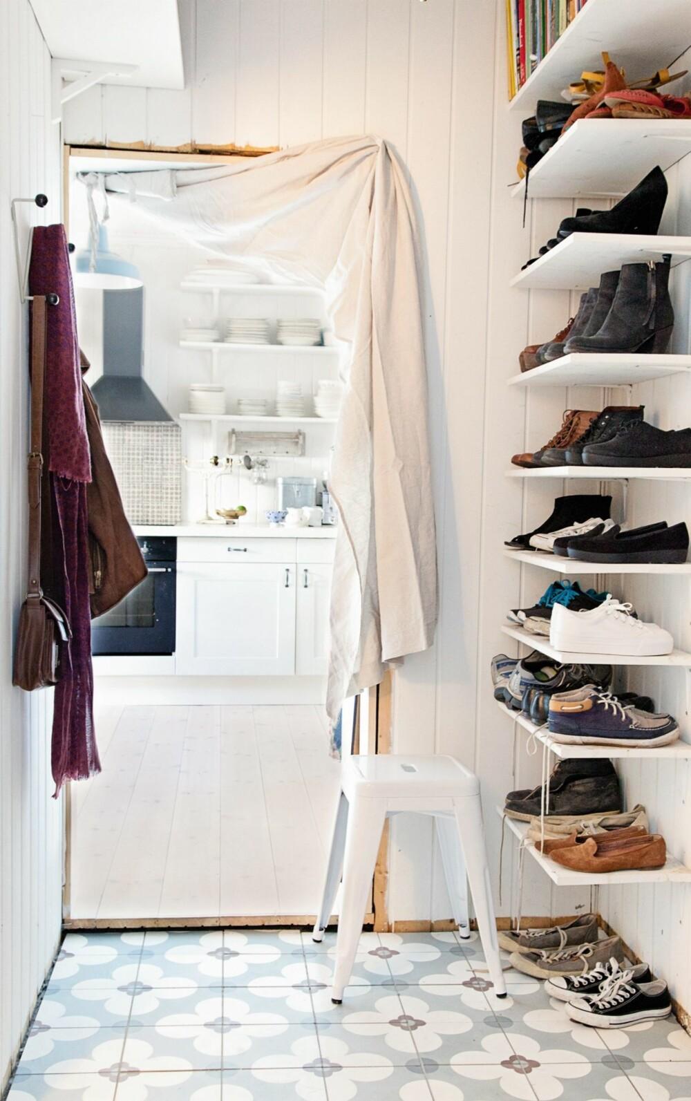 GJENNOMFØRT STIL: Fliser fra Gamle Trehus bringer stilen videre til gangen. Helene og Vegard har bygget praktiske hyller fra gulv til tak for å få plass til alle sko.
