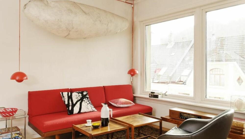 """Den stramme sofaen er produsert av Ekornes, trekket er nytt. Den mumielignende kokongen på veggen er en gave fra en kunstnervenn. Eikegulvet er av typen """"Line"""", med stavene montert på høykant for økt slitestyrke."""