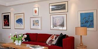 De hvite veggene får liv gjennom alle kunstbildene som strekker seg fra salongen, og helt bort til kjøkkenet. Beboeren har valgt å leke seg med møbler i ulike farger og fasonger.