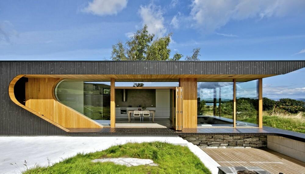 FULL FART OVER ARKITEKTUREN I ROGALAND: Arkitekt Tommie Wilhelmsen har tegnet  hytta på Rennesøy. De mørkbeisete veggene har oljet eik i de inntrukne partiene. Takutstikket skjermer og forhindrer at det blir for varmt inne i hytta sommerstid.