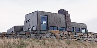 ET BORGAKTIG KYSTHUS : Se hvordan Frøya sommerhuset presser seg ned mot bakken med skrå vegger nesten hele veien rundt.