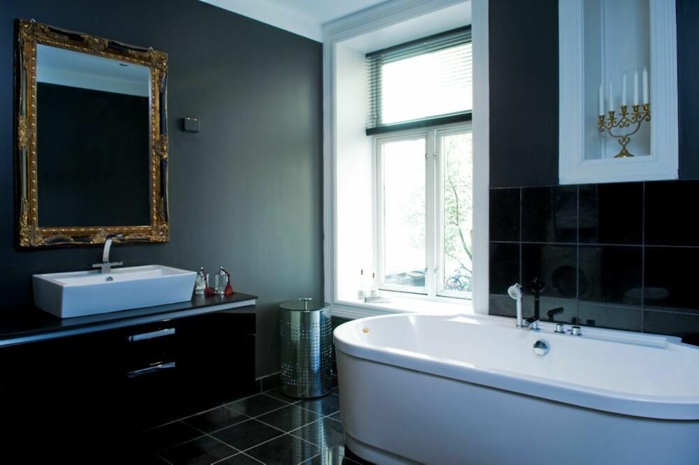 FARGEN ENDRER SEG: Den svarte fargen på badet endres med lyset i løpet av dagen. Noen ganger oppleves den med et ispedd av grønt. Speilet på veggen og de svarte flisene skaper sammenheng med resten av stilen i leiligheten. Innredningen er fra Kvik, og speilet er fra Skeidar. Badekaret er kjøpt over Internett på www.dittnyebad.no.