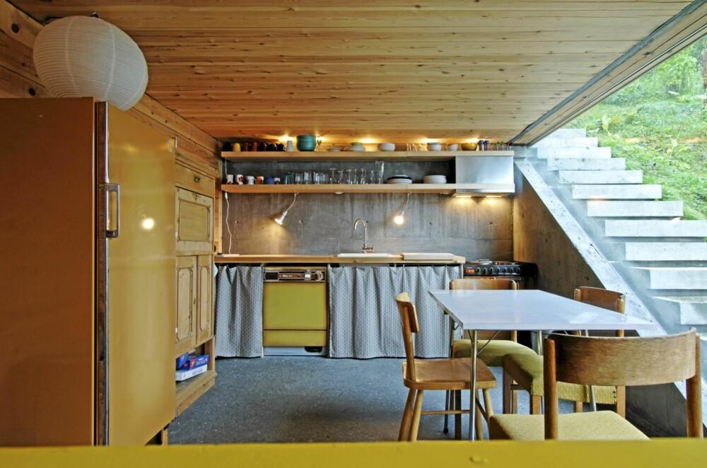TETT SAMSPILL MED TERRENGET: Kjøkkenet i allrommet i annen etasje har gulbrune syttitalls hvitevarer som matcher tilbygget. Det slipte betonggulvet har vannbåren varme. Utetrappen til høyre går langs hele huset og ender ved den store terrassen i tredje etasje.