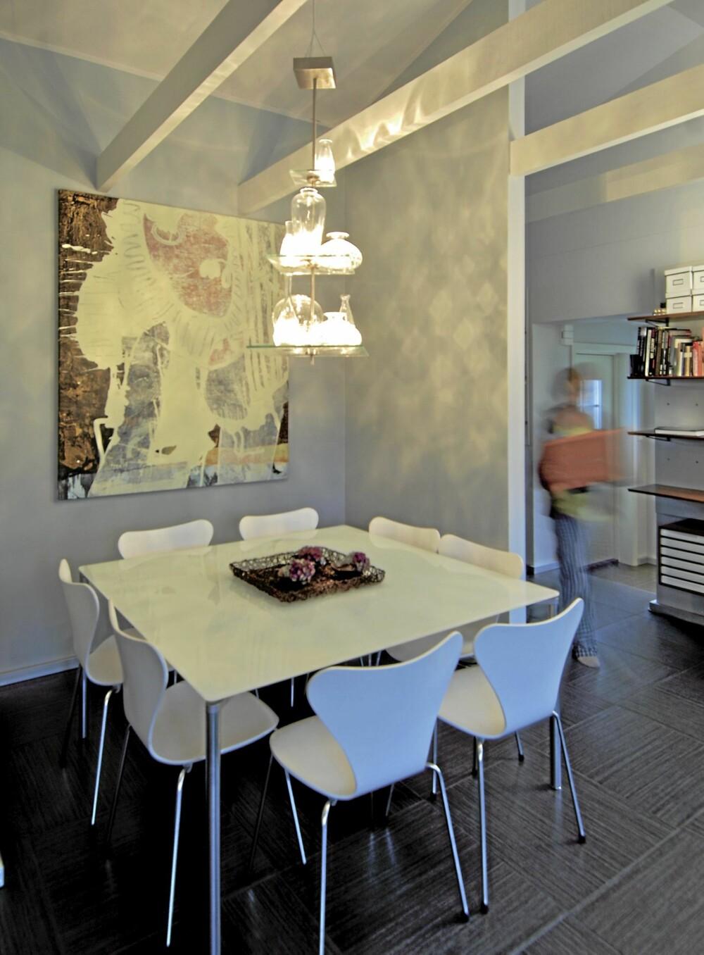 SKJERMET SONE: Glitrende lysspill. Spisestuen danner en skjermet sone ved kjøkkenavdelingen. Philippe Starcks taklampe gir et skimrende fargespill på veggene og fremhever maleriet. Glassbord fra Fritz Hansen. Gulvet er dekket av store gulvfliser fra Viva, «X-ILO», Fagflis.