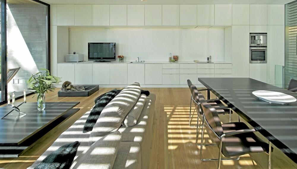GJENNOMGÅENDE: Et av de mest markante elementene i boligen er løsningen med musikkbenk som går over i kjøkkenbenk for så å slutte i en baderomsinnredning (t.h bak persiennen).