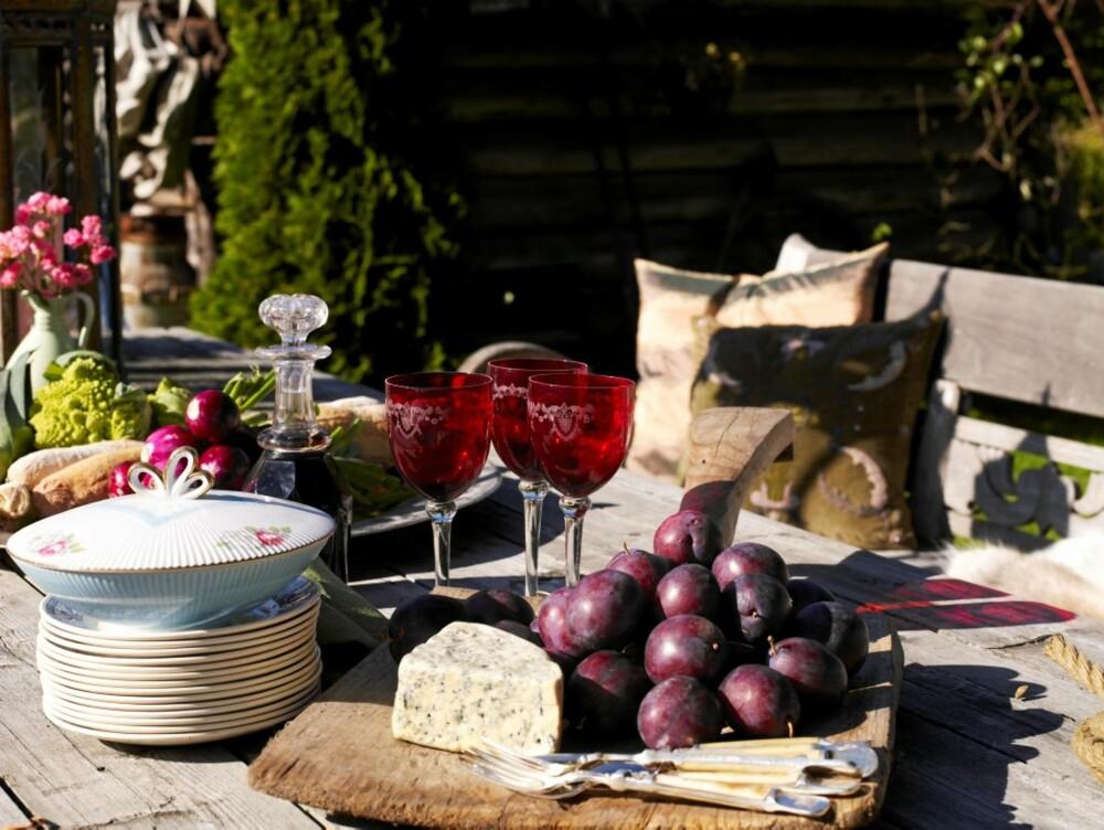 NYTER LIVET: Vibeke inviterer gjerne venner og familie til uhøytidelig lunsj på tunet.. Da dekker hun opp med porselen og krystall på det rustikke bordet og fyller benkene med skinnfeller, pledd og puter.