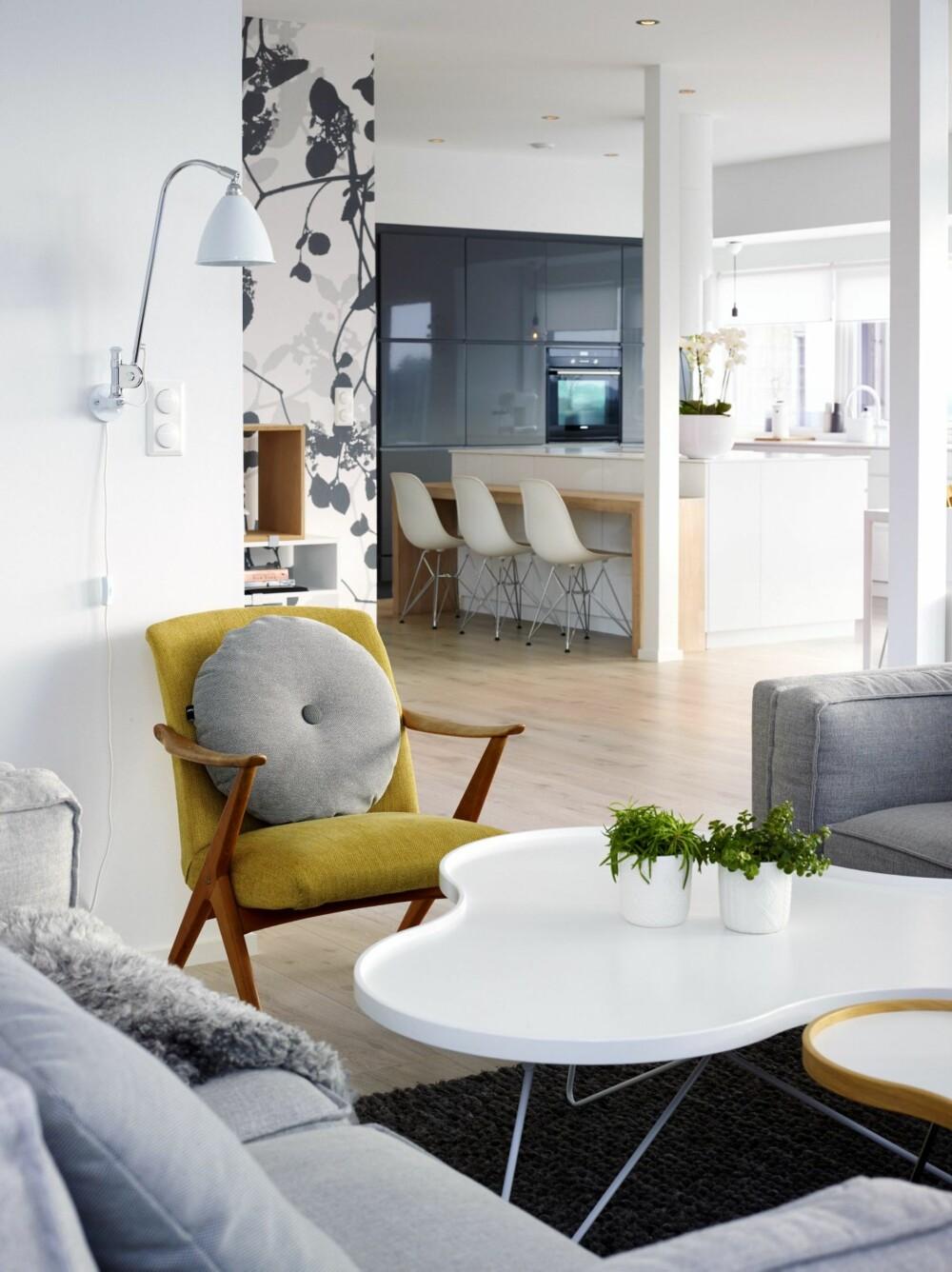 LANGE LINJER: Takhøyden i stuen er på 3,4 meter. Kjøkkenet er fra Kvik, med benkeplate i Corian bestilt på mål fra Tyskland. Lenestolen er et bruktfunn. Gulvteppet er fra Hay. For å skape dynamikk i det åpne rommet, valgte Janne å tapetsere en vegg med mønstret tapet fra Scandinavian Surface.