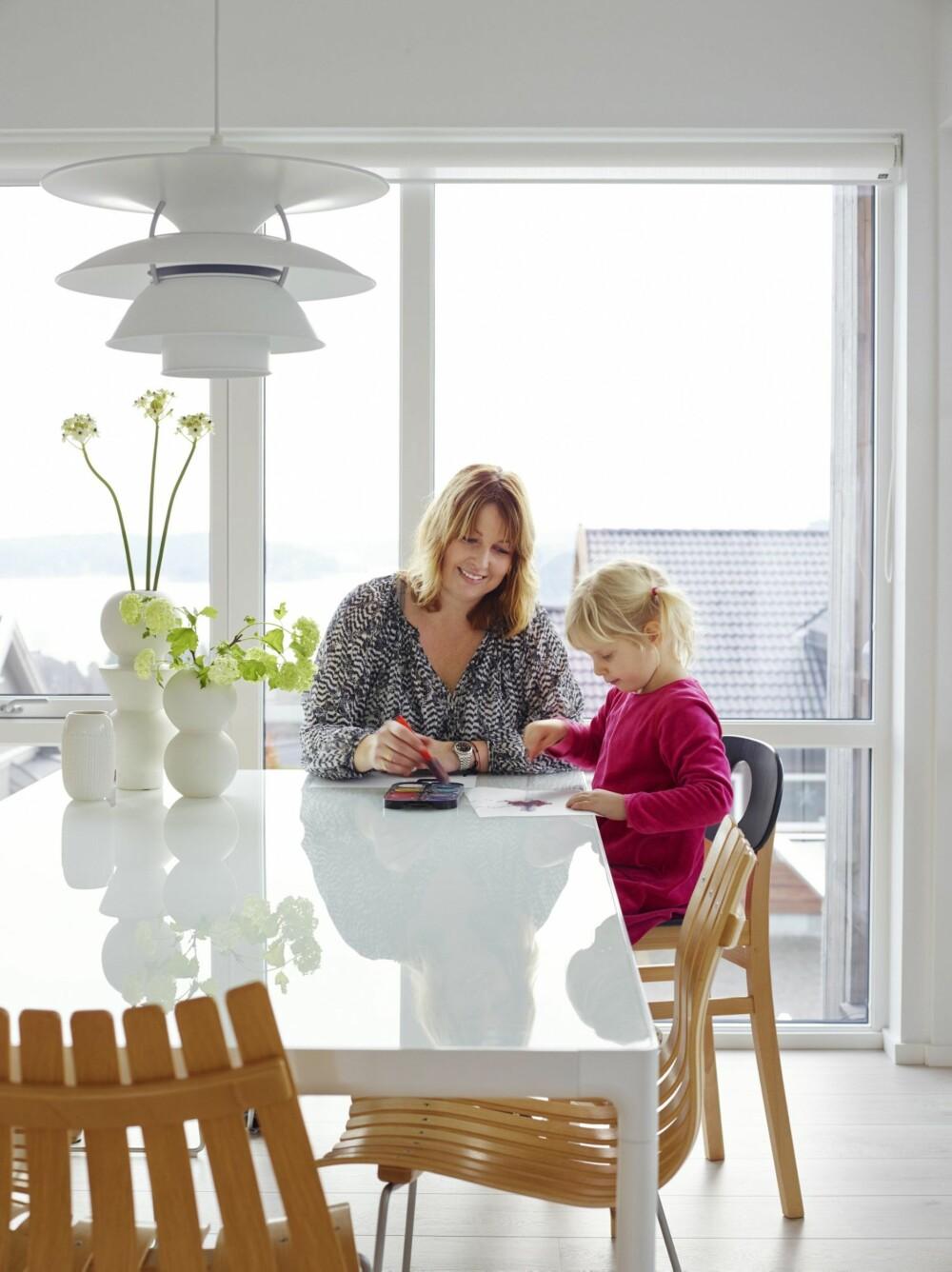FINT LYS: Janne og datteren Olivia ved spisebordet fra danske Danerka, med nedfelt glassplate. Scandia-stolene er en norsk klassiker, designet i 1957 av Hans Brattrud. Blomstervaser fra Ferm Living og PH-lampe fra Louis Poulsen.