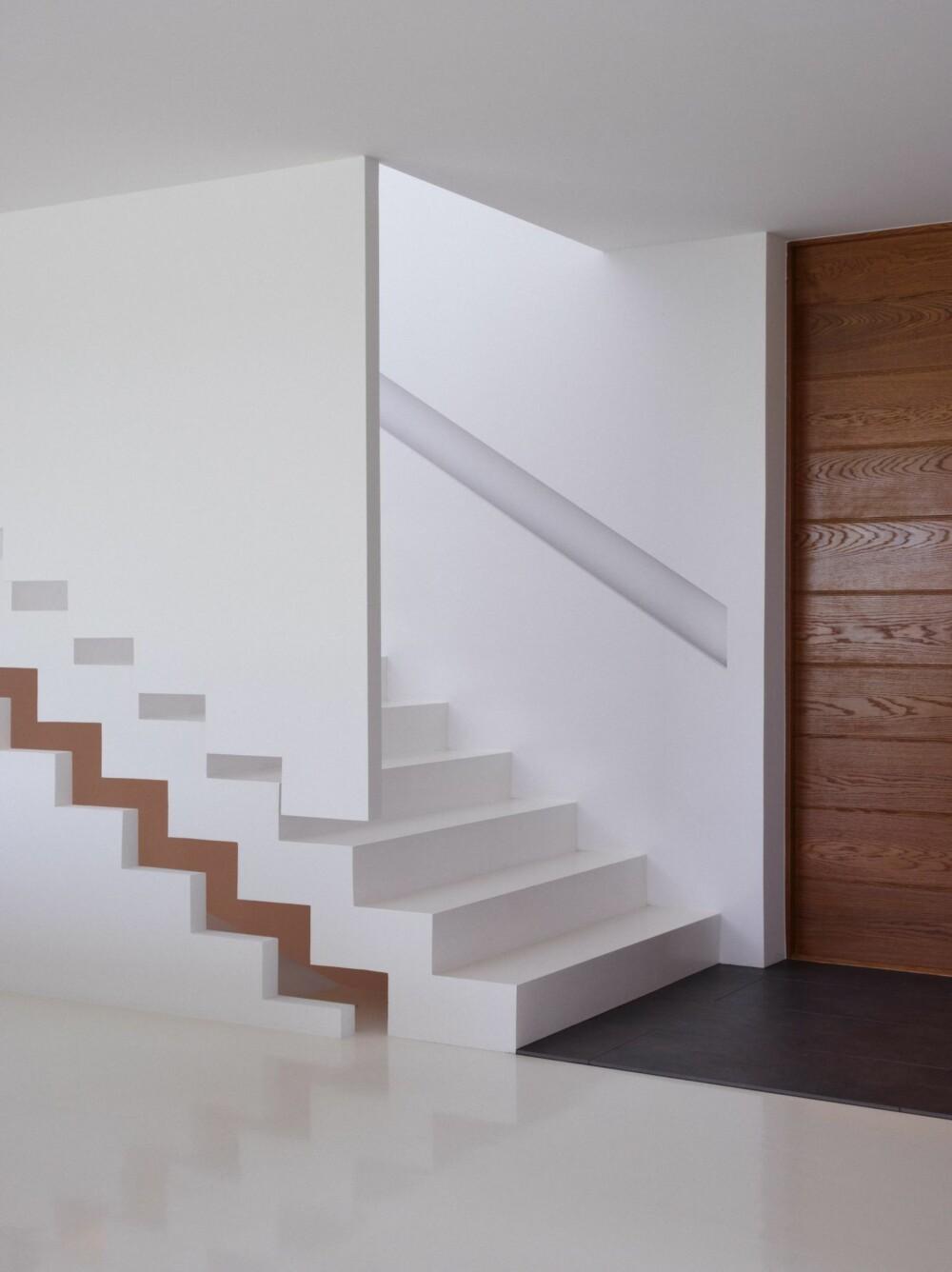 DETALJERT: Til høyre er inngangsdøren i eik, levert av svenske SnickarPer. Det innfelte trappegelenderet har neonlys som kan skifte farge mellom rosa, blått og grønt. Den hvite veggen med trappemønster skulle vært av glass, men budsjettet tok slutt. En av håndverkerne foreslo denne luftige løsningen, som falt i god jord.