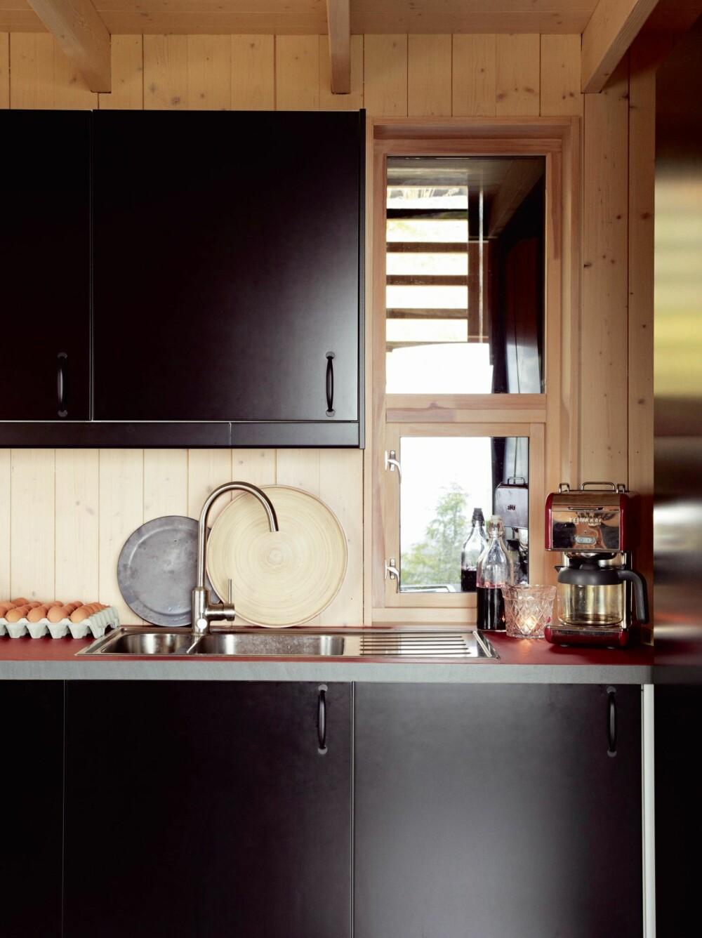 MØRKT MOT LYST: Kjøkkenet er svart fordi vi liker kontraster, og kjøkkenbenken er belagt med linoleum, som tåler heftig hyttebruk, sier Kari. Innredningen er fra Ikea.