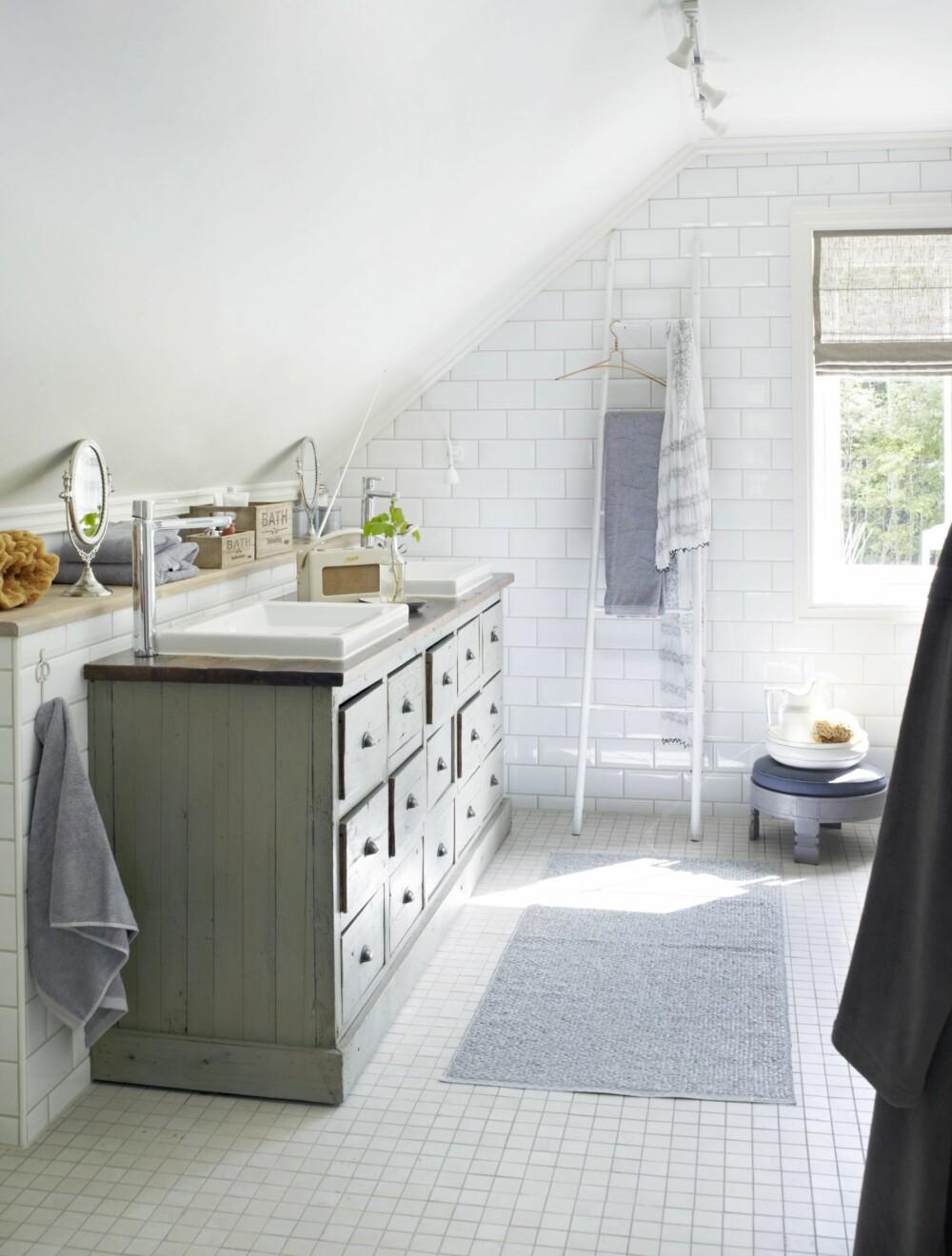 Fremhev gulvet ved å sette kontrasterende materialer mot det. Kjøpmannsdisken er fra Home & Cottage, platen er lakket med åtte strøk, slik at den tåler vannsøl. Vaskene er fra Duravit, og stigen er fra Ha det på badet. Plastmatte fra Palma, krakk fra HK Living. Badekaret er rammet inn med klassiske metrofliser fra Flisekompaniet, gulvflisene er fra Megaflis.