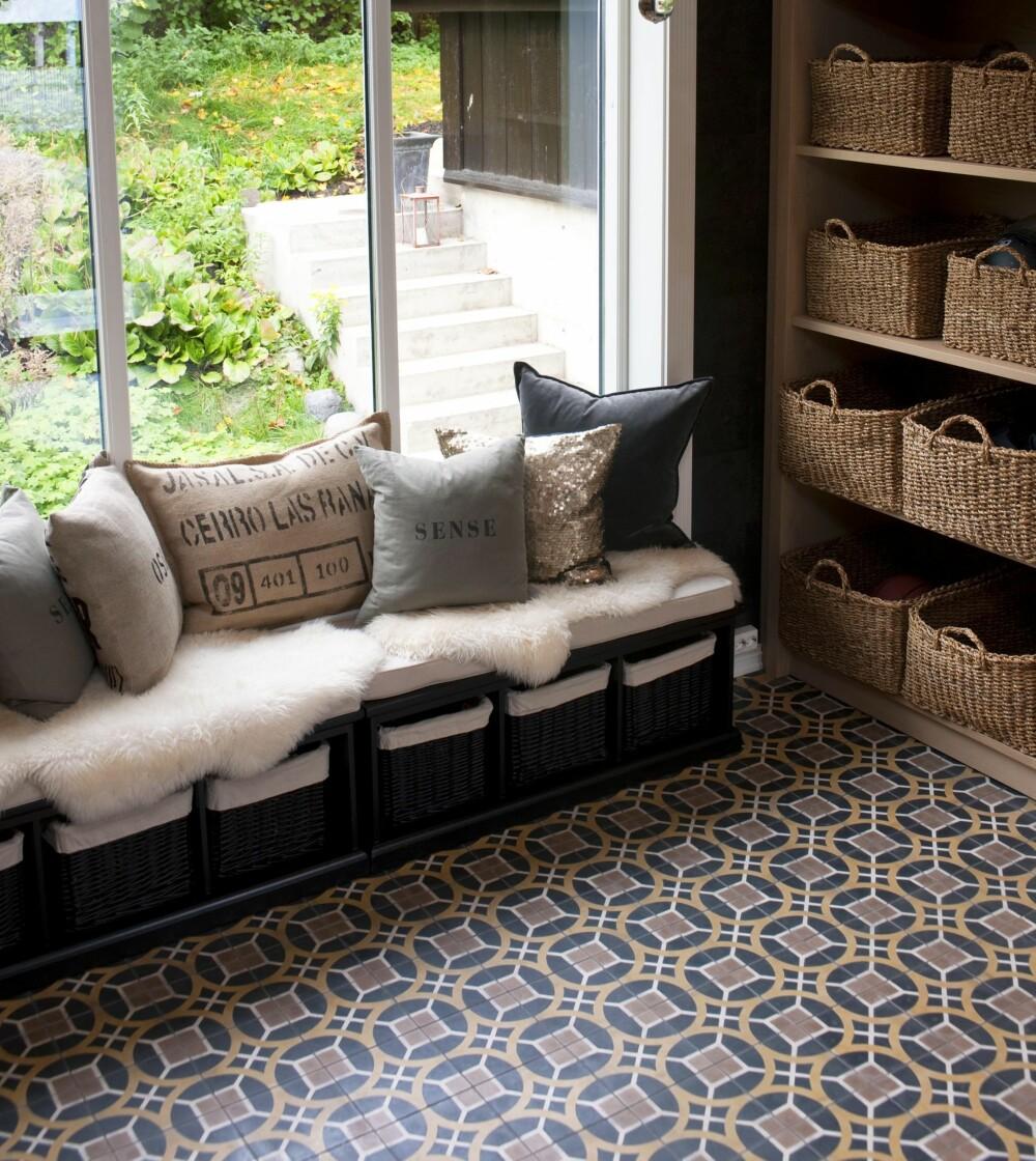 Gulvet i hallen er kledd med marokkanske fliser fra marrakechdesign.se. Kurver er satt på hyllene og gir plass til luer og sokker. Det er også satt kurver under sittebenken. Puter og skinn myker opp stramme linjer.