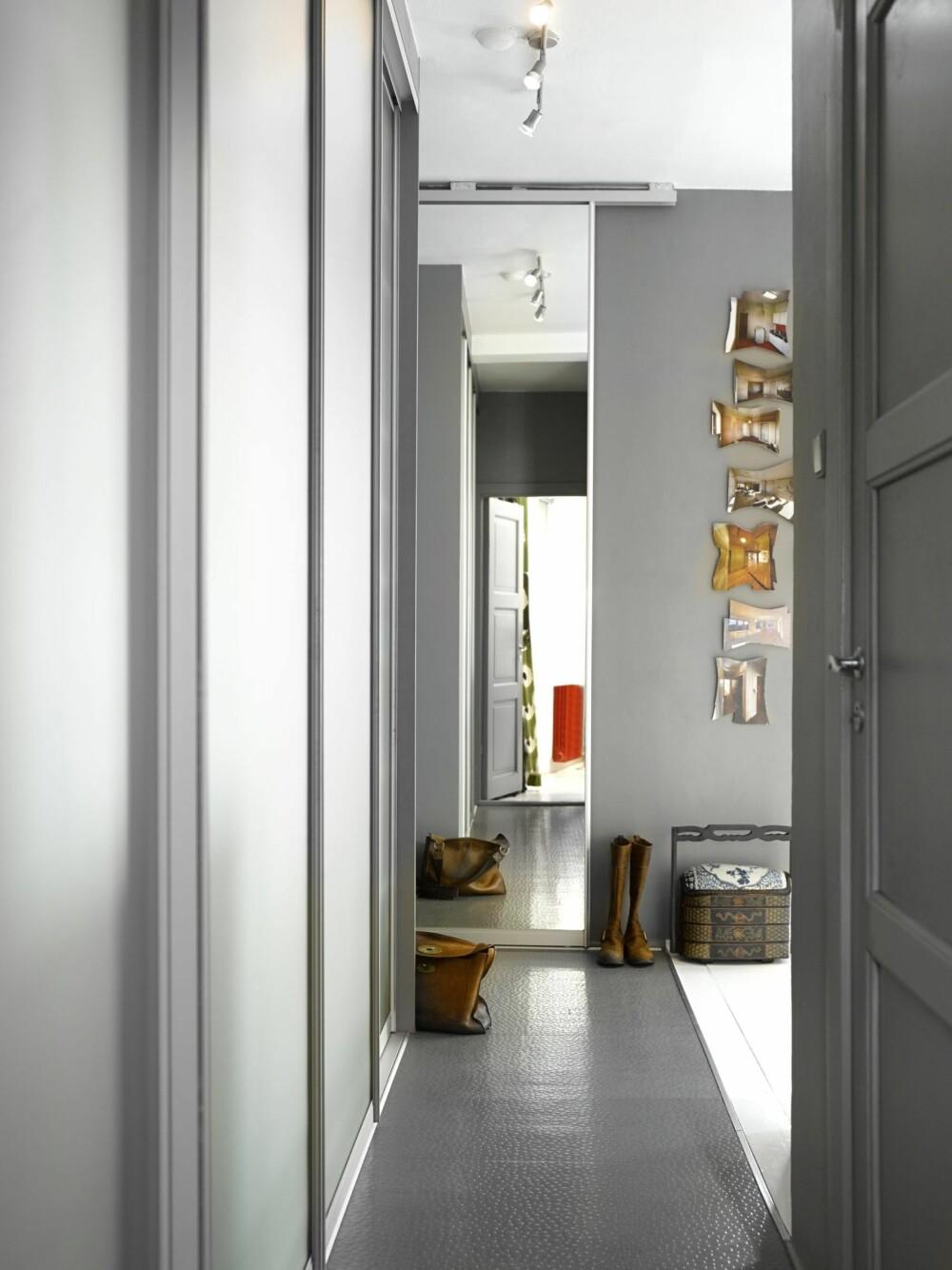 FIN EFFEKT: Speilet er en skyvedør, bak den ligger garderobeskap. Kontoret speiles i fronten, til høyre er det åpne kjøkkenet. Grått linoleumsbelegg tåler en støyt og gjennomført fargebruk fremhever rommenes linjer. Bildene på veggen viser leiligheten før renoveringen.