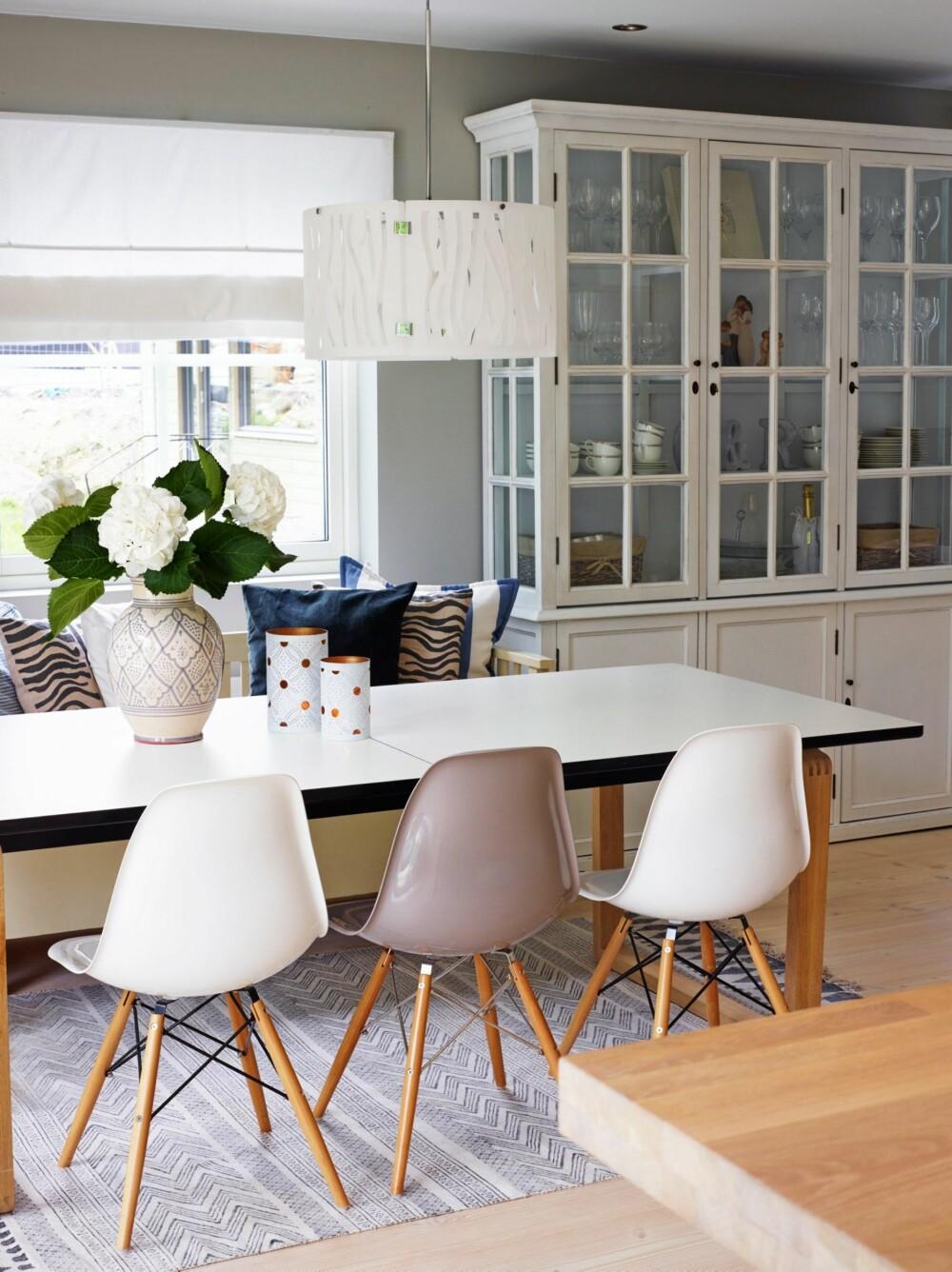 DUS PALETT: Teppet fra House Doctor, taklampen Gras fra Herstal og vitrineskapet fra Home and Cottage skaper en trivelig ramme rundt de stramme spisestuemøblene. Eames-stolene er kjøpt fra England, mens spisebordet er fra Bolia. Den marokkanskinspirerte vasen er fra TineKHome.