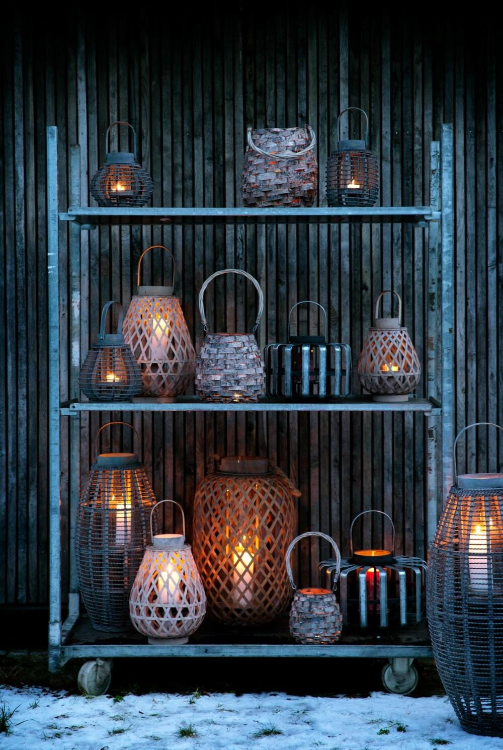 TRE, BAMBUS OG GLASS: Flettede lanterner myker opp lyset fra flammene. Glasskolber på innsiden sørger for at lyset brenner ufortrødent i vinden, kr 120 - 1085, brostecopenhagen.com. På en hylle langs husveggen er for tiden en populær og effektfull måte å plassere utelyktene på.