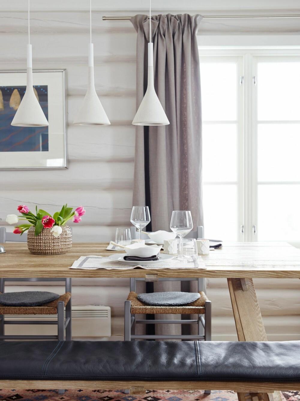 GOD BLANDING: Spisebordet og benken har hun hatt i flere år. Jærstolene malte Marianne i NCS S 4000 N. Betonglampene over bordet kler fargen på tømmerveggene, samtidig som de gir kontrast i materialbruken. Lampene er fra Foscarini. Styling: Tone Kroken.