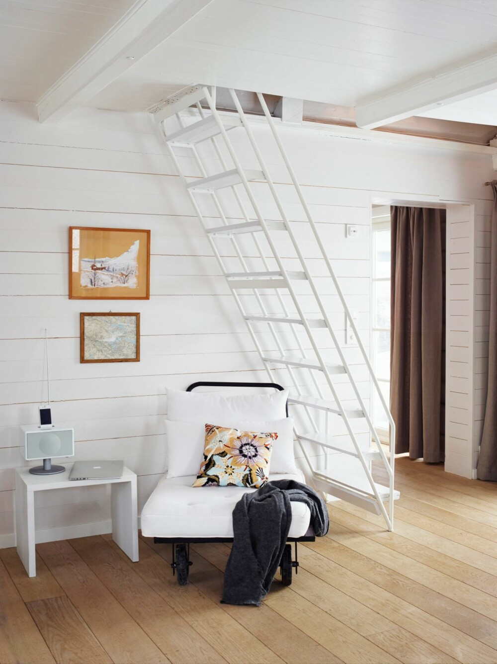 PLASSBESPARENDE: Trappen opp til sovehemsene er tegnet og bygget av Mariannes bestefar, da han eide hytta. Avslapningsstolen er fra Palma. Bildene er gamle kart, blomstret pute fra Missoni. På gulvet er det brede planker i eik. Styling: Tone Kroken.
