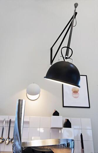 GIR ARBEIDSLYST: For å få god arbeidsbelysning over kokesonen, er det benyttet en kombinasjon av nedhengte pendler og veggmontert belysning. Lampen 265 fra Flos kan lett skyves bort når den ikke er i bruk.