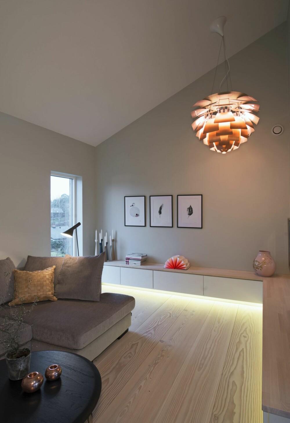 KLASSISK MIDTPUNKT: I TV-stuens hjørne er PH-konglen plassert under den høye himlingen, og kaster kobberfarget lys på veggene. Den er plassert slik at den også er et midtpunkt på fasaden sett utenfra. Skapstammene er overskap fra en kjøkkeninnredning, supplert med en benkeplate i douglasgran fra Dinesen. Innredningen følger hjørnet i rommet og forsterker rommets form. Under er det montert en LED-list som gjør at benken får et lett, svevende uttrykk. Ifølge beboerne er led-stripen nede helt ideell når de ser på tv fordi bildetfremstår tydelig. Led-stripen kan for øvrig kjøpes metervis. Den mørkegrå leselampen er AJ fra Louis Poulsen.