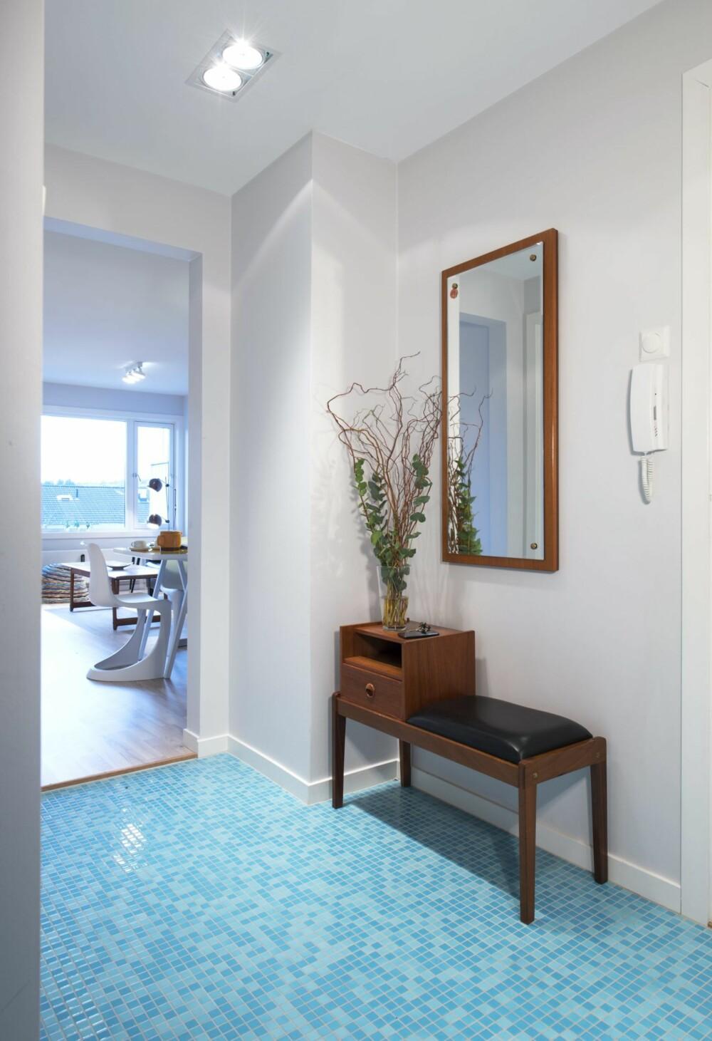LUFTIG OG LYST: Døren til stuen er fjernet, og lyset flommer inn i den vindusløse gangen. Beboerne fortsetter å dyrke 50-, 60-tallsstilen som var her da de flyttet inn, og som speiler tiden leiligheten ble bygget i. Mosaikkfliser på gulvet forbindes oftest med baderom, men kan beviselig også benyttes i andre rom som er utsatt for særlig vannsøl og slitasje. Flisene i paletten Siros er fra Cesiceramica, Flisekompaniet.