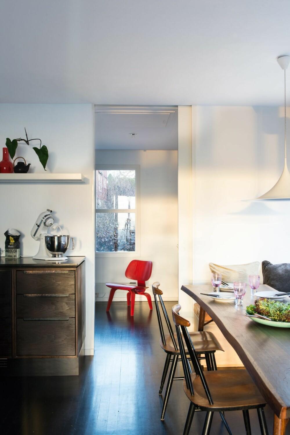 LANGE LINJER: Rommet innenfor allrommet benyttes som tv-stue. Rommet kan lukkes ved hjelp av en skyvedør. Men som regel står den oppe, for å sluse lyset på kryss og tvers her oppe i annenetasjen. Den rødbeisede stolen LCW er fra Vitra. Styling: Juni Hjartholm.