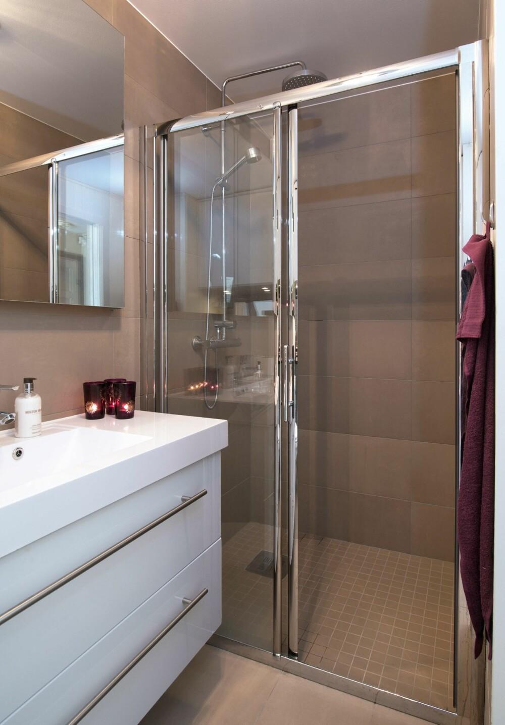 KLAR VEGG: Ved dusjen ble det valgt skyvedører i glass. Det gjør rommet tettere, men er en praktisk løsning som minimerer vannsøl. Skyvedører fra Holtan Trading. Servant med skuffer er Lind Monaco fra Megaflis. I våtsonen er det benyttet avlange, store fliser på veggen og små på gulvet. For øvrig er det mdf-plater på veggene der det ikke er vannsøl.
