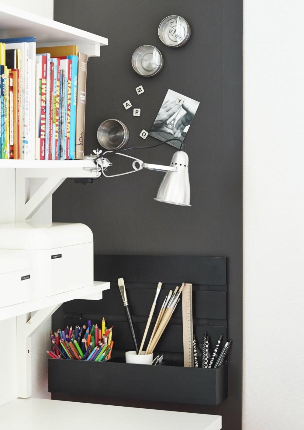 EFFEKTFULLT: Den svarte tavlen består av en MDF-plate som er tapetsert med magnettapet, fra Borge, og malt svart, S 8000-N. Den svarte boksen i tre til blyanter og skrivesaker er kjøpt på salg hos Granit. Klemmespoten Fas, kr 98, og de hvite oppbevaringsboksene er fra Ikea. Styling: Steen & Aiesh, stylingassistent: Ida Løken.