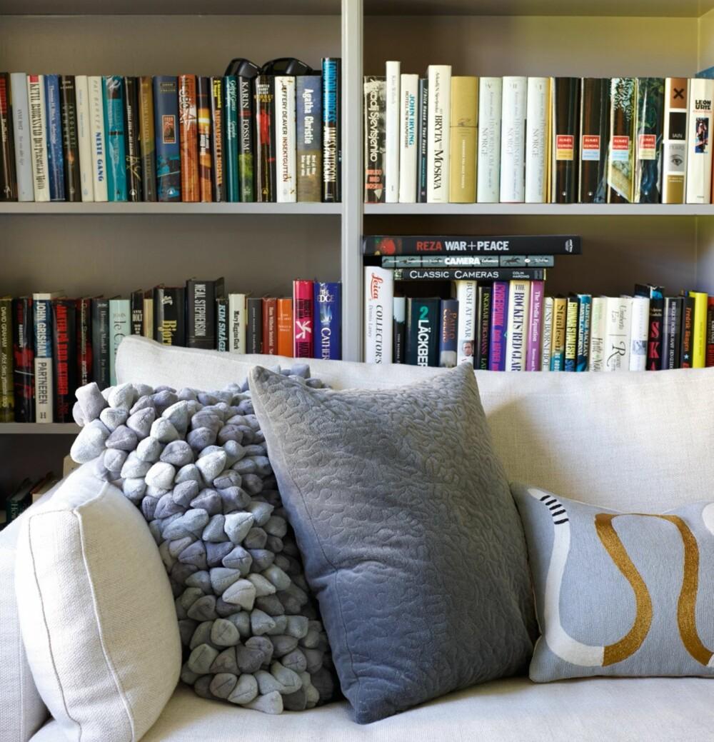 LUNT: Biblioteket i flukt med stuen hadde plassbygde bokhyller som sammen med veggene ble malt i en ren grå farge med fargenummer NCS 3500 N. Putene er fra Palma og Expo Nova.