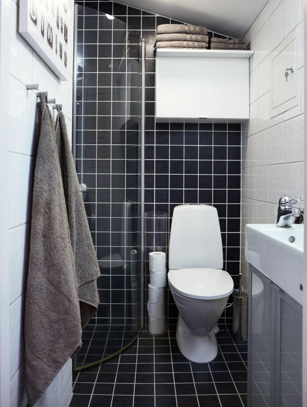BRUK FARGE PÅ BAD: Den usedvanlig smale vasken, 20 x 70 cm, ble et funn for dette lille badet, den er fra Ikea. Ved dusjen er det montert en halvpart av et 90 cm dusjhjørne. Veggen er svingbar og kan dyttes helt inn mot veggen når dusjen ikke er i bruk. Nye, svarte fliser gir inntrykk av dybde i rommet.