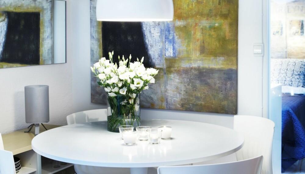 KROK FOR FIRE: Innerst mot veggen er takhøyden knappe 1,60 cm. En spisegruppe er langt mer praktisk her enn en kjøkkenbenk slik det var tidligere. Det runde bordet i plast, Ø 110 cm, er fra Ikea, mens stolene er norsk design kjøpt på salg hos Paustian. Pendelen over bordet er blant dem som kan monteres i skråtak, fra Lampemagasinet. Veggspeilet, egentlig en skapdør det ikke ble plass til på soverommet, gjør at hjørnet virker rommeligere. Glassfeltet i veggen mot soverommet slipper inn dagslys i den litt dunkle kroken. Skjenken er en pimpet tv-benk som er forsynt med høyere ben og sagd av i bakkant slik at den bare er 40 cm dyp. Maleriet ble kjøpt på et marked fordi det hadde varme, fine farger som kunne passe her.