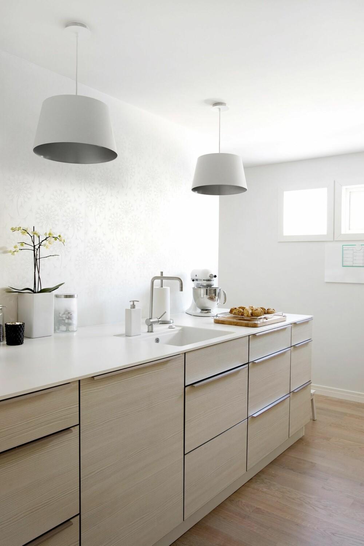 SOM I STUEN: Med glatte fronter og rene flater, kan kjøkkenet fort skape en klinisk atmosfære, kanskje ikke den stemningen man ønsker seg av et oppholdsrom. Ved å bringe inn noen stofflige, gjerne stueaktige pendler over kjøkkenbenken, motvirkes det tekniske, kjølige preget uten å fire på lyskvaliteten. Kjøkkenet er fra Kvik, tapetet heter Eco White-tapet og pendelene kommer fra Bolia.