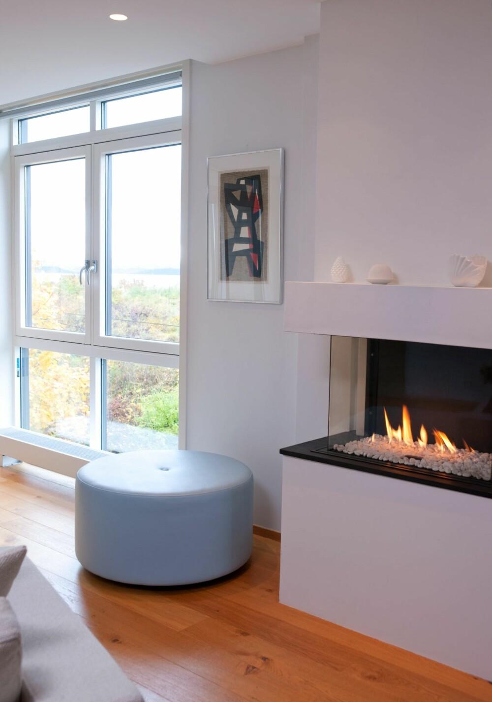 LYSEBLÅ TRÅD: Den lyseblå fargen representerer himmel og hav, og går igjen flere steder i boligen, blant annet på puffen som interiørarkitekten har designet.