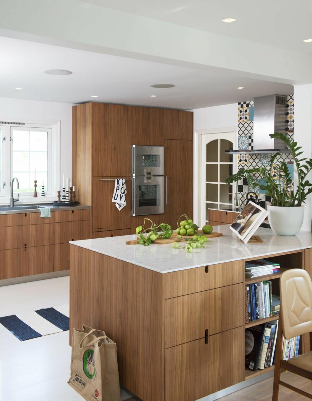 GJENNOMTENKT: Vasken ved vinduet har benkeplate i stål. Oppvaskmaskinen er plassert i skapet hvor kjøkkenhåndkleet henger på håndtaket. Matten på det malte furugulvet kommer fra Pappelina. Kokebokstativ fra Åhléns. Kjøkkenhåndkle med bokstaver, design Arne Jacobsen, kjøpt på Bolina. Styling: Juni Hjartholm.